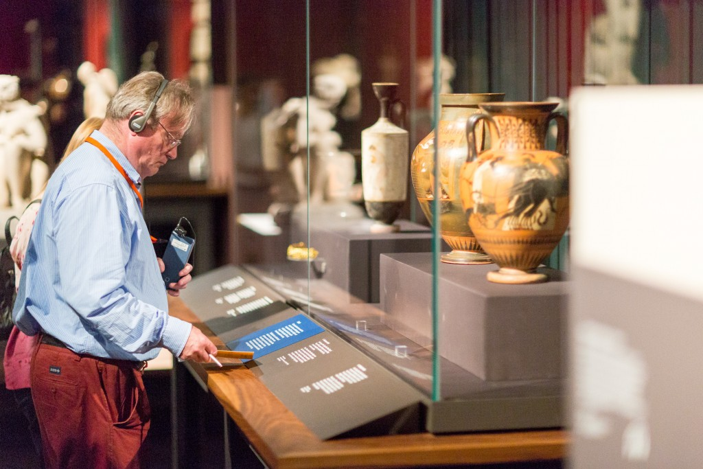Visitor looks carefully at an object label