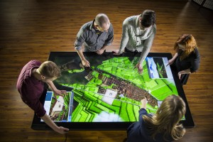 Five users gather around a large multitouch table displaying a 3D model of Cusco