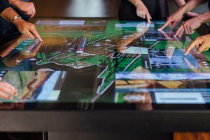 A 3D model of Cusco and media windows are visible on a large multitouch table