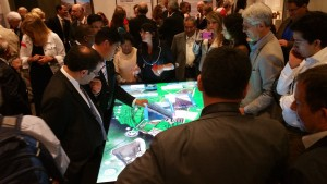 A crowd of people surrounds the 84-inch multitouch table displaying a 3D model of Cusco.