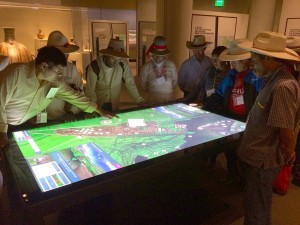 A crowd of bridge builders visiting NMAI from Peru navigate the 3D model