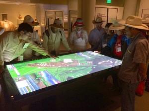 A crowd of bridge builders visiting NMAI from Peru navigate the 3D model