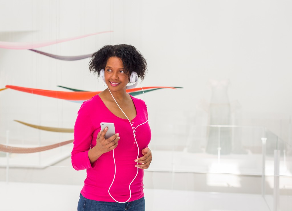 A woman stands in a museum gallery with her mobile phone and headphones